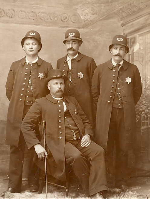 Little Falls Police Force of 1890.  Chief Thomas Bailey, Jake Mrozik, William Tourtillot, and John Roy.  Little Falls, Minnesota, went from being a village to becoming a city in 1889, thus making these men some of the earliest official order-keepers for the city.