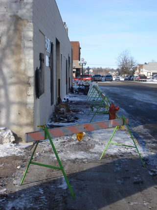 View of the sidewalk after the fire, Bills Decorating & Iron Hills Pawn Shop, Little Falls, MN, January 26, 2010. Theres evidence of fire damage on the sidewalk.