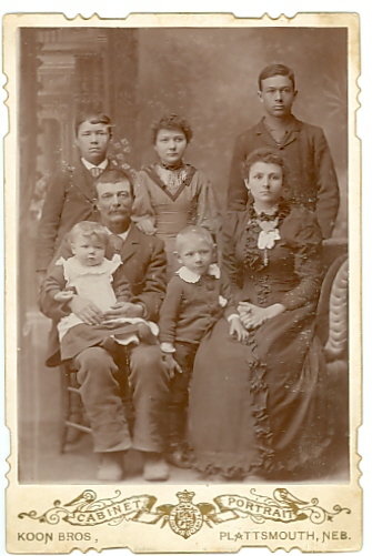 Clifton Tidds father, S. D. Tidd, and step-mother, Minnie Colbow Tidd.  Back row, left to right:  Clifton, Nancy, Charlie, children of S. D. Tidd and Mary Cutlipp Tidd.  Robert, sitting on S. D.s lap, belongs to S. D. and Minnie.  Archie Colbow, standing between, is Minnies son.  Photo by Koon Bros., Plattsmouth, Nebraska, c. 1892-93.