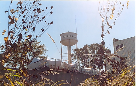 Little Falls water tower, located on Seventh Avenue NE, next to Little Falls City Hall.  Dismantled November 8, 2006, after being replaced by a larger water tower in northeast Little Falls.  Photo taken from behind and below Larson Motor Service.  Photo by Mary Warner, October 2003.